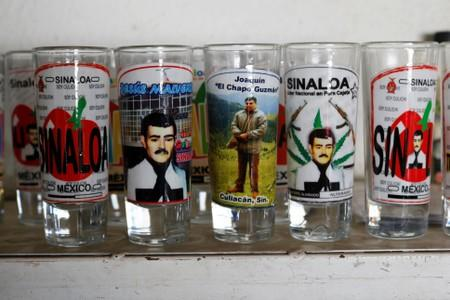 "Votive candles with the images of Mexican drug lord Joaquin ""El Chapo"" Guzman (C) and ""Saint Jesus Malverde"" are pictured at a stall outside the ""Saint Jesus Malverde"" chapel in Culiacan"