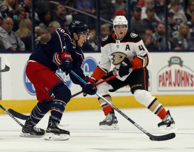 Columbus Blue Jackets forward Sonny Milano, left, controls the puck in front of Anaheim Ducks defenseman Josh Manson during the first period of an NHL hockey game in Columbus, Ohio, Friday, Oct. 11, 2019. (AP Photo/Paul Vernon)