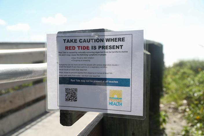 A sign warns about Red Tide
