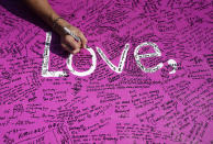 A Britney Spears supporter signs a poster board for the singer outside a hearing concerning the pop singer's conservatorship at the Stanley Mosk Courthouse, Wednesday, Sept. 29, 2021, in Los Angeles. (AP Photo/Chris Pizzello)