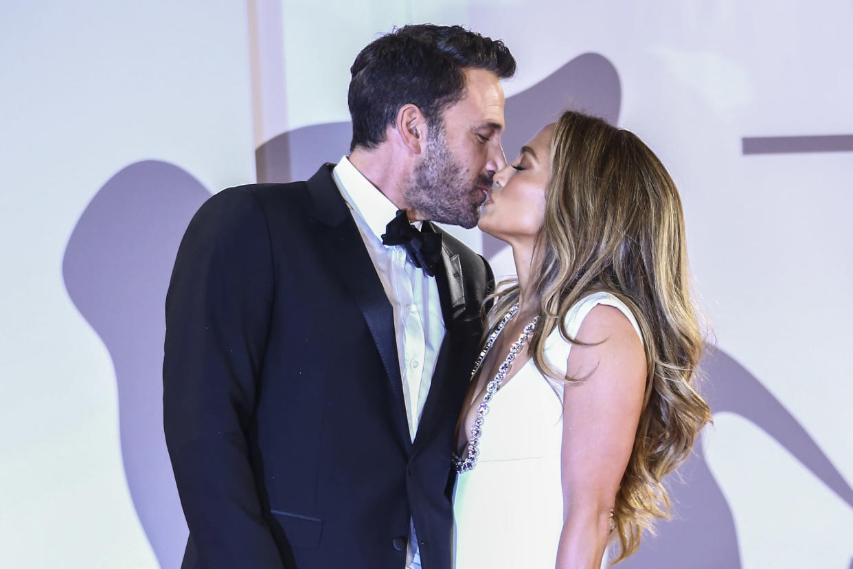Jennifer Lopez and Ben Affleck kiss during their first red carpet since getting back together. (Photo: AP)