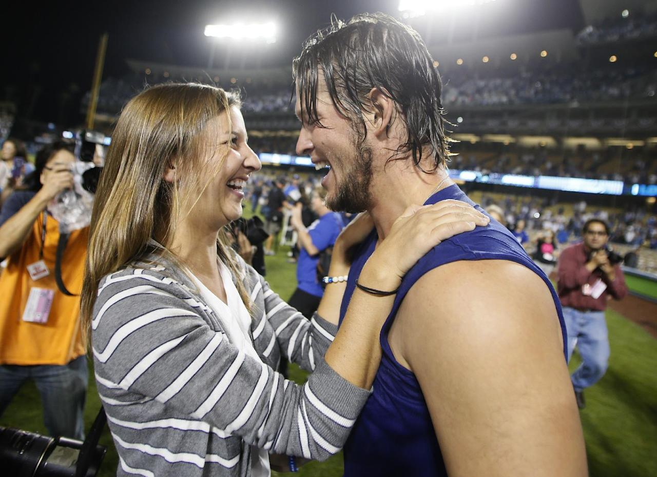 Los Angeles Dodgers starting pitcher Clayton Kershaw, right, greets his wife, Ellen, left, after the Dodgers defeated the Atlanta Braves 4-3 in Game 4 of the National League baseball division series Monday, Oct. 7, 2013, in Los Angeles. The Dodgers advanced to the NL championship series. (AP Photo/Danny Moloshok)