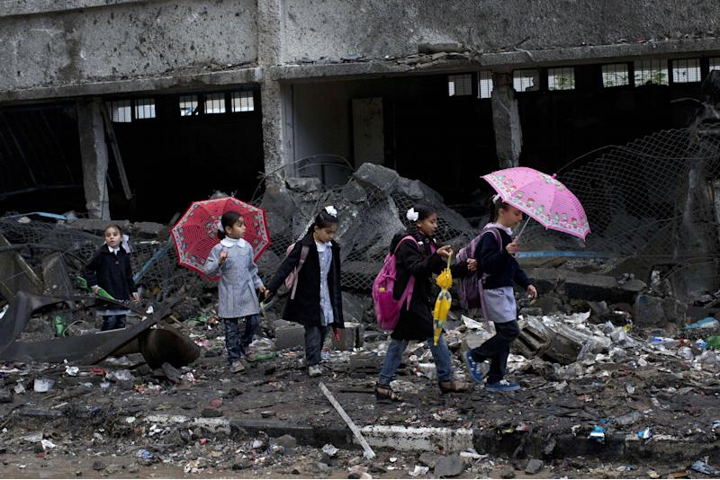 FILE - In this Nov. 24, 2012 file photo Palestinian schoolchildren walk in debris by a damaged school in Gaza City. In a report published Feb. 12, 2013, Human Rights Watch, a U.S.-based rights group said Israel violated laws of war in a series of airstrikes during an eight-day military operation last November against the Hamas militant group in the Gaza Strip.(AP Photo/Bernat Armangue, File)