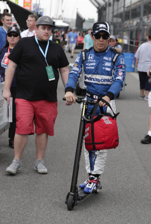 Takuma Sato, of Japan, rides a scooter back to the garage area on the opening day of practice for the Indy 500 auto race at Indianapolis Motor Speedway in Indianapolis, Tuesday, May 15, 2018. (AP Photo/Michael Conroy)