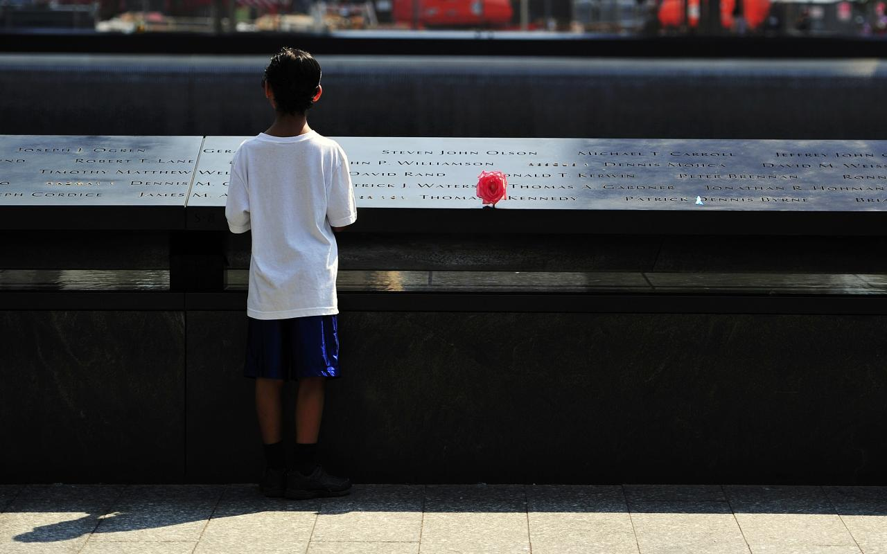 A boy looks at names on the South reflecting pool at the 9/11 Memorial during ceremonies marking the 12th anniversary of the 9/11 attacks on the World Trade Center in New York, September 11, 2013. REUTERS/Stan Honda/Pool (UNITED STATES - Tags: ANNIVERSARY DISASTER)