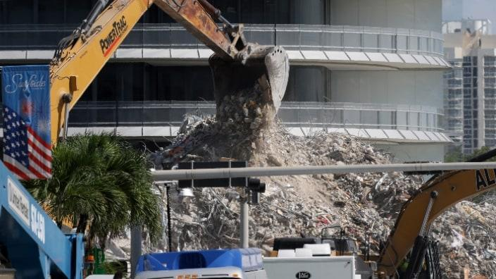 Construction equipment is used to dig through the mound of debris from the collapsed 12-story Champlain Towers South condo building last month in Surfside, Florida. (Photo by Anna Moneymaker/Getty Images)