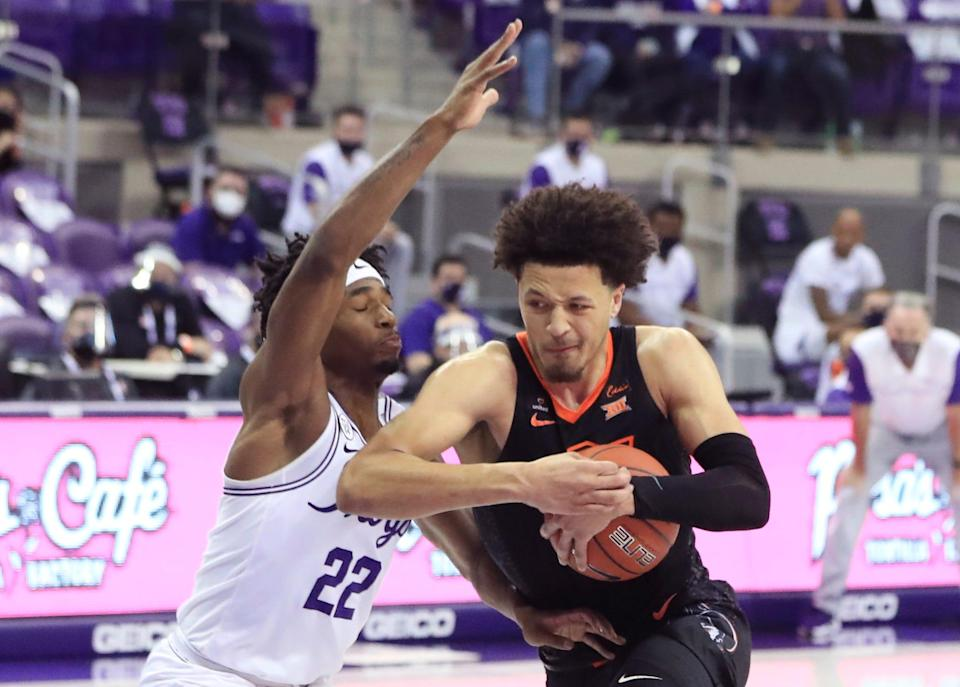 Oklahoma State's Cade Cunningham drives to the basket as TCU's RJ Nembhard defends Feb. 3, 2021 in Fort Worth, Texas.