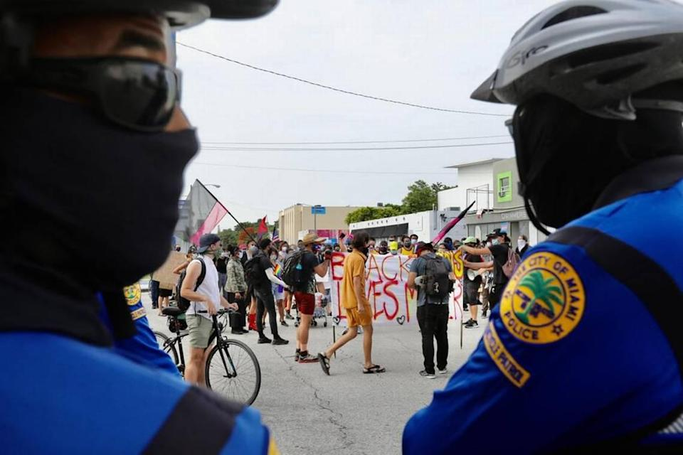 """Miami police watch in Wynwood during the """"Pride riot"""" on Sunday on June 28, 2020, marking the 51st anniversary of the beginning of the 1969 Stonewall riots in New York City to advance LGBTQ rights."""