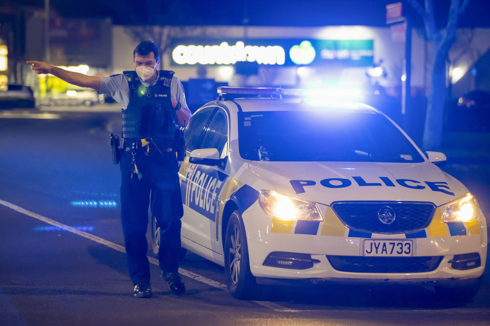 FILE - In this Sept. 3, 2021, file photo, a police officer gestures as he stands outside the site of a knife attack at a supermarket in Auckland, New Zealand. New Zealand politicians on Thursday, Sept. 30, 2021, passed a law that makes plotting a terrorist attack a crime, fixing a legal loophole that was exposed earlier this month by a violent knife attack. (AP Photo/Brett Phibbs, File)
