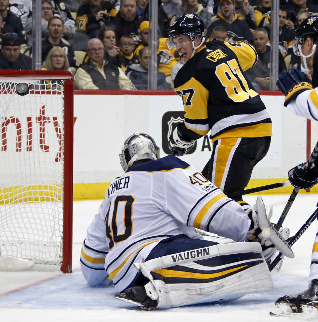 Pittsburgh Penguins' Sidney Crosby (87) lifts the puck over Buffalo Sabres goalie Robin Lehner (40) for a goal in the second period of an NHL hockey game in Pittsburgh, Tuesday, Nov. 14, 2017. (AP Photo/Gene J. Puskar)