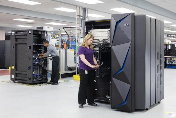 Employees working on two IBM z14 mainframe systems.