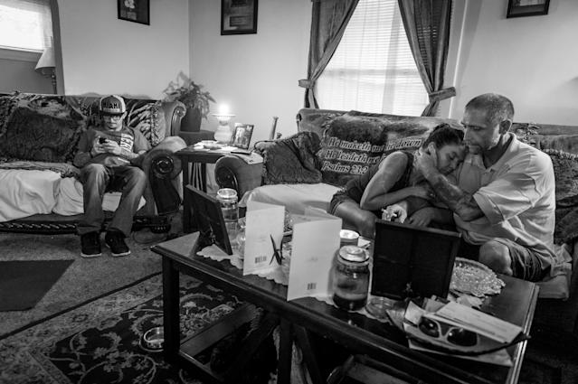 <p>Gene Robinson, right, caresses his wife Terri Fugate while Terri's son Larry Fugate, far left, looks at his phone in their Middletown, Ohio home. Both men are recovering heroin addicts.<br> (Photograph by Mary F. Calvert for Yahoo News) </p>