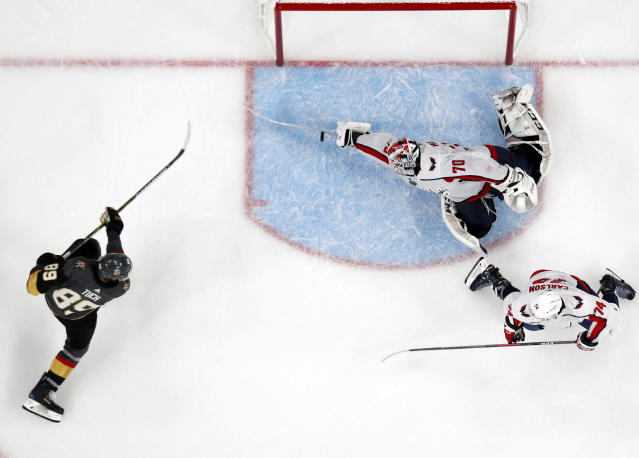 Washington Capitals goaltender Braden Holtby, center, makes a stick save on shot by Vegas Golden Knights right wing Alex Tuch, left, as defenseman John Carlson watches during the third period in Game 2 of the NHL hockey Stanley Cup Finals on Wednesday, May 30, 2018, in Las Vegas. (AP Photo/John Locher)