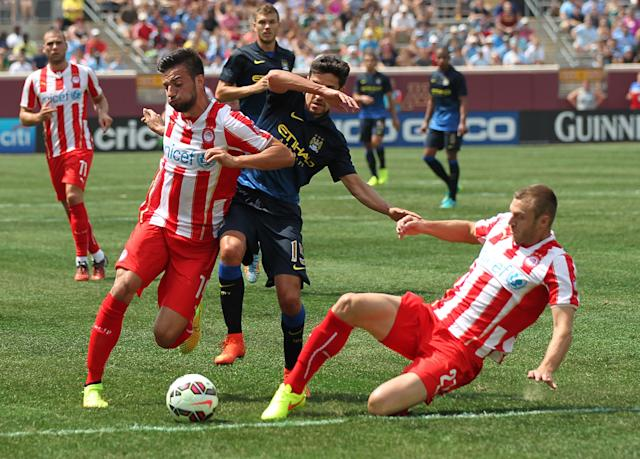 Manchester City midfielder Jesus Navas (15), center, is converged on by Olympiacos forward Kevin Mirallas (14), left, and Olympiacos defender Giannis Maniatis (2) during the first half of the Guinness International Champions Cup at TCF Bank Stadium on the University of Minnesota campus in Minneapolis, Saturday, Aug. 2, 2014.(AP Photo/Andy Clayton-King)