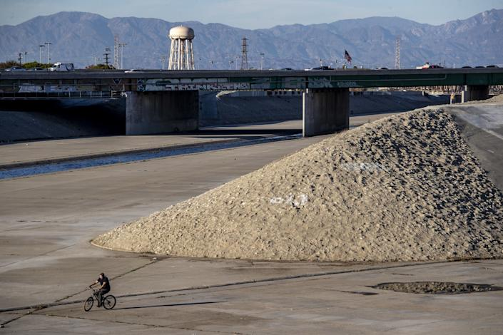 A cyclist rides in the Los Angeles River near what might be Confluence Point Park Sunday, Jan. 10, 2021 in South Gate.