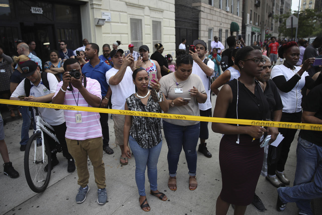 <p>Onlookers take photos outside Bronx Lebanon Hospital where a gunman opened fire and then took his own life there, Friday, June 30, 2017, in New York. The gunman, identified as Dr. Henry Bello who used to work at the hospital, returned with a rifle hidden under his white lab coat, law enforcement officials said. (AP Photo/Mary Altaffer) </p>