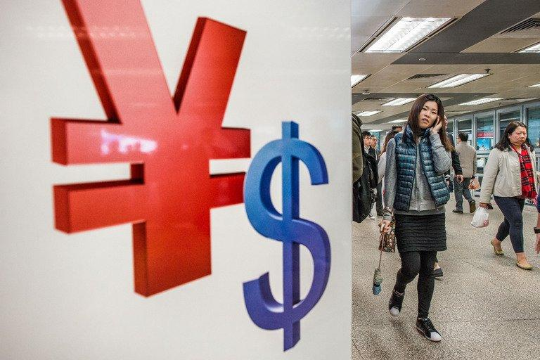 A woman walks past Chinese yuan and US dollar symbols in Hong Kong on November 28, 2012
