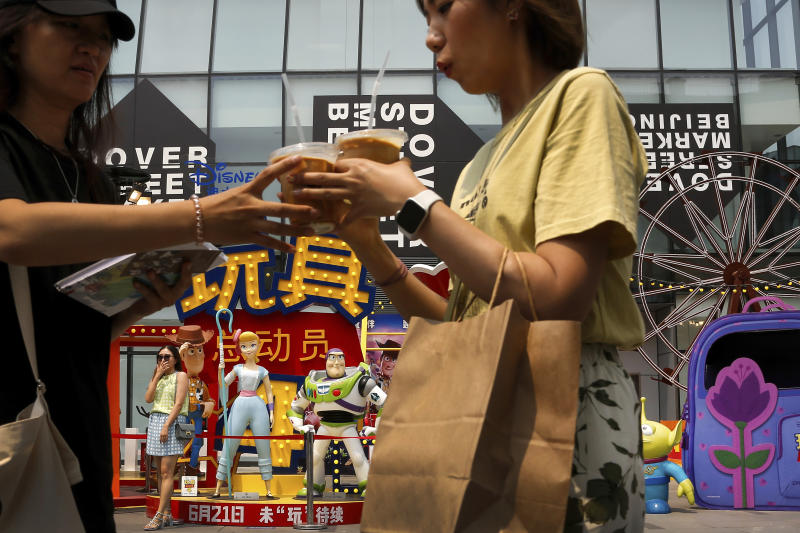 "Women stand near the American latest animated film ""Toy Story 4"" characters on display at the capital city's popular shopping mall in Beijing, Tuesday, June 25, 2019. China says its trade negotiators are talking to their U.S. counterparts on how to resolve disputes ahead of an expected meeting between their two heads of state at the G20 meeting in Japan later this week. (AP Photo/Andy Wong)"