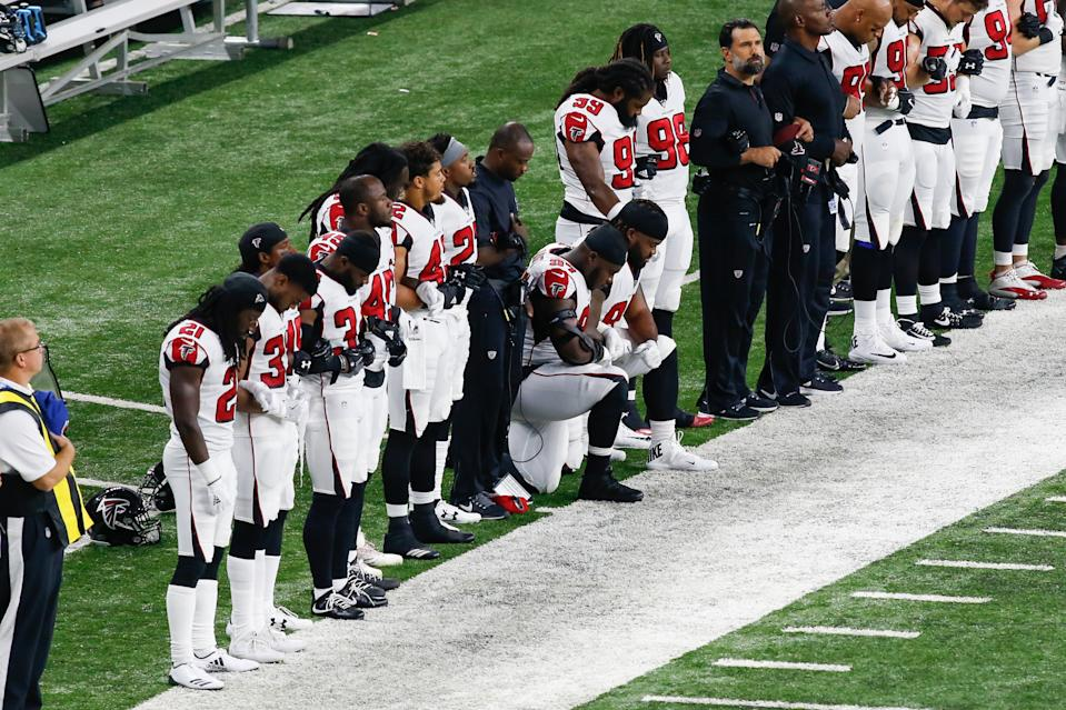Atlanta Falcons' Grady Jarrett and Dontari Poe kneel during the national anthem during a 2017 game.