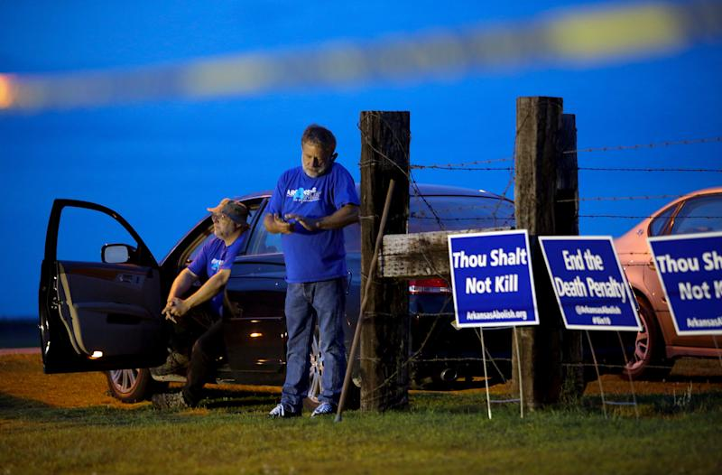 "Anti-death penalty supporters Abraham Bonowitz, left, and Randy Gardner wait near their taped off ""protest corral"" outside the Varner Unit - Credit: AP"
