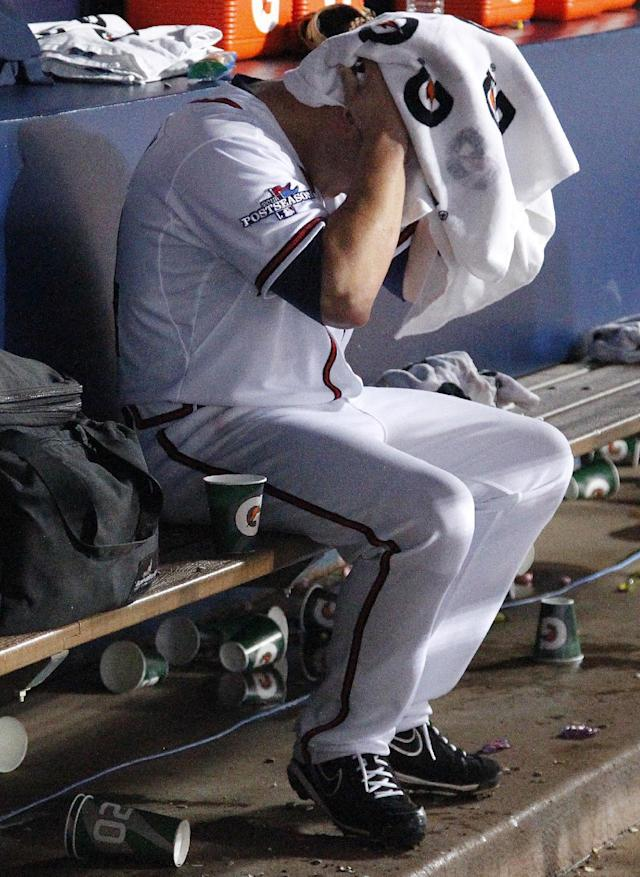 Atlanta Braves starting pitcher Kris Medlen (54) dries off in the dugout after being relieved in the fifth inning of Game 1 of the National League Division Series against the Los Angeles Dodgers, Thursday, Oct. 3, 2013, in Atlanta. (AP Photo/Mike Stewart)