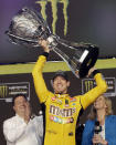 Kyle Busch holds up his trophy in Victory Lane after winning a NASCAR Cup Series auto racing season championship on Sunday, Nov. 17, 2019, at Homestead-Miami Speedway in Homestead, Fla. (AP Photo/Terry Renna)