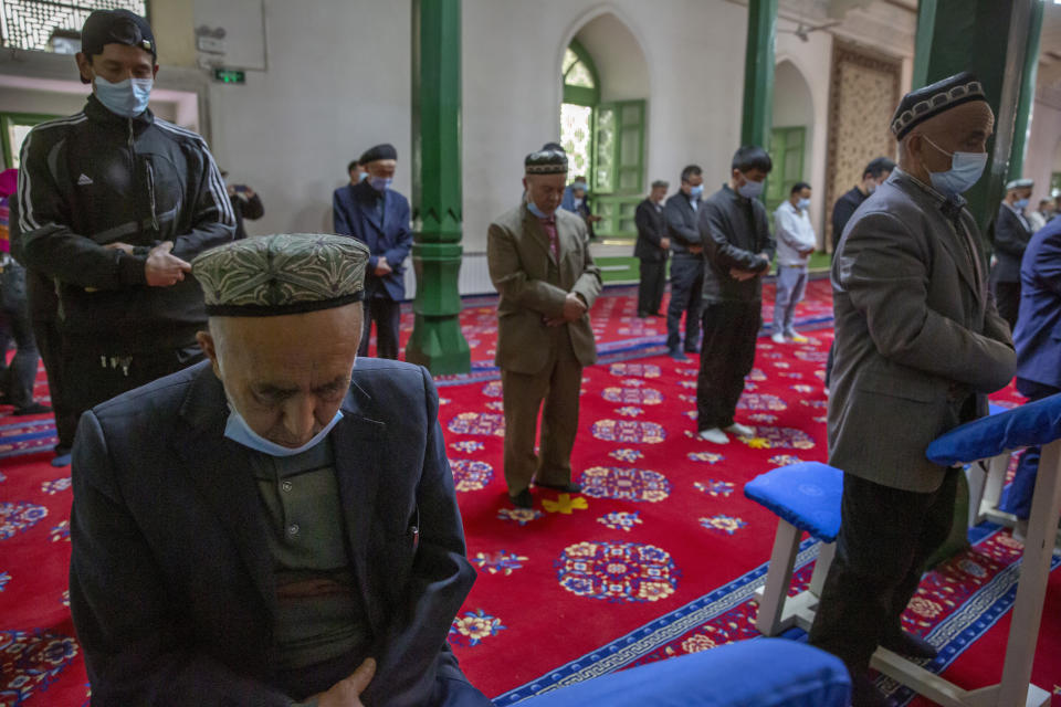 Uyghurs and other members of the faithful pray during services at the Id Kah Mosque in Kashgar in far west China's Xinjiang region, as seen during a government organized visit for foreign journalists on April 19, 2021. Four years after Beijing's brutal crackdown on largely Muslim minorities native to Xinjiang, Chinese authorities are dialing back the region's high-tech police state and stepping up tourism. But even as a sense of normality returns, fear remains, hidden but pervasive. (AP Photo/Mark Schiefelbein)