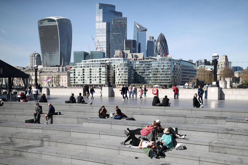 <p>People enjoying the warm weather at City Hall near Tower Bridge in central London last Friday</p> (PA)