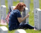 Mom hugs tombstone of son at the Ohio Western Reserve National Cemetery on Memorial Day in Seville