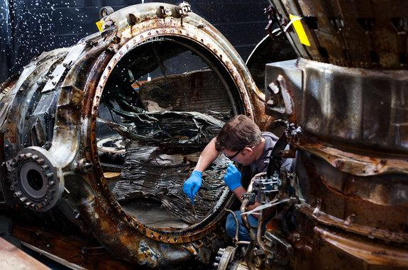 SpaceWorks technician Jerrad Alexander uses a brush to clean an F-1 engine thrust chamber at the Kansas Cosmosphere. In the background, the mist from one of the sprays treating the artifacts with freshwater to remove ocean debris.