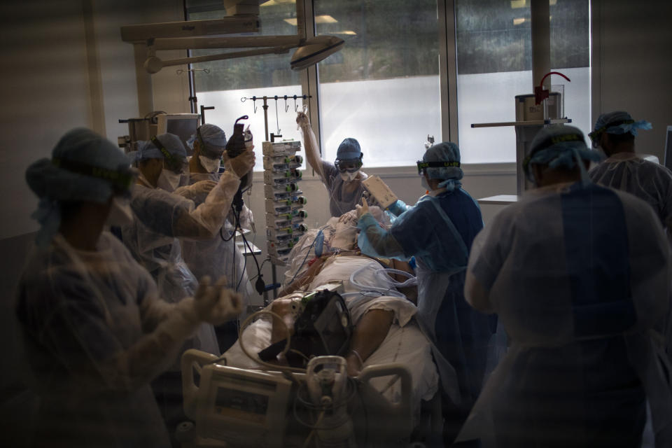 Medical workers begin installing a 60-year-old COVID-19 patient into an ICU room with oxygen and dialysis machines after he was transferred to the main ICU at the La Timone hospital in Marseille, southern France, from a makeshift wing that was unable to continue supporting his worsening condition on Thursday, Nov. 12, 2020. (AP Photo/Daniel Cole)