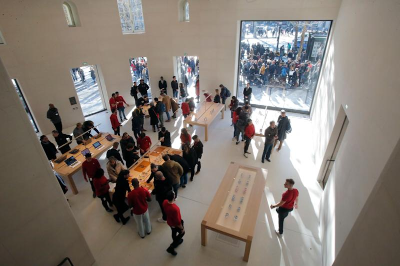 Customers stroll in side the new Apple store at the Champs Elysees avenue in Paris, France, Sunday, Nov. 18, 2018. Apple open today its latest retail location at the Camps Elysees avenue. (AP Photo/Michel Euler)