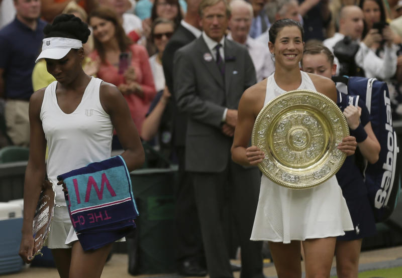 Venus Williams of the United States, left leaves with her runner-up trophy from Centre Court after her defeat by Spain's Garbine Muguruza, right, in Women's Singles final on day twelve at the Wimbledon Tennis Championships in London Saturday, July 15, 2017. (AP Photo/Tim Ireland)