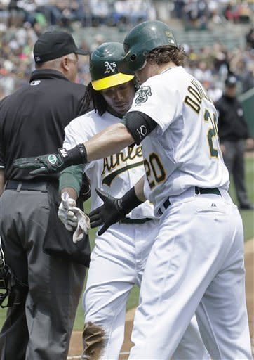 Oakland Athletics' Jemile Weeks, center, is congratulated by Josh Donaldson after scoring on a single by Jonny Gomes against the New York Yankees during the first inning of a baseball game in Oakland, Calif., Saturday, May 26, 2012. (AP Photo/Jeff Chiu)