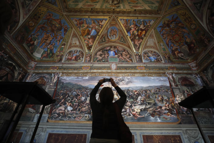 A visitor admires a Raphael Room inside the Vatican Museums on their reopening, in Rome, Monday, May 3, 2021. The Vatican Museums reopened Monday to visitors after a shutdown following COVID-19 containment measures. (AP Photo/Alessandra Tarantino)
