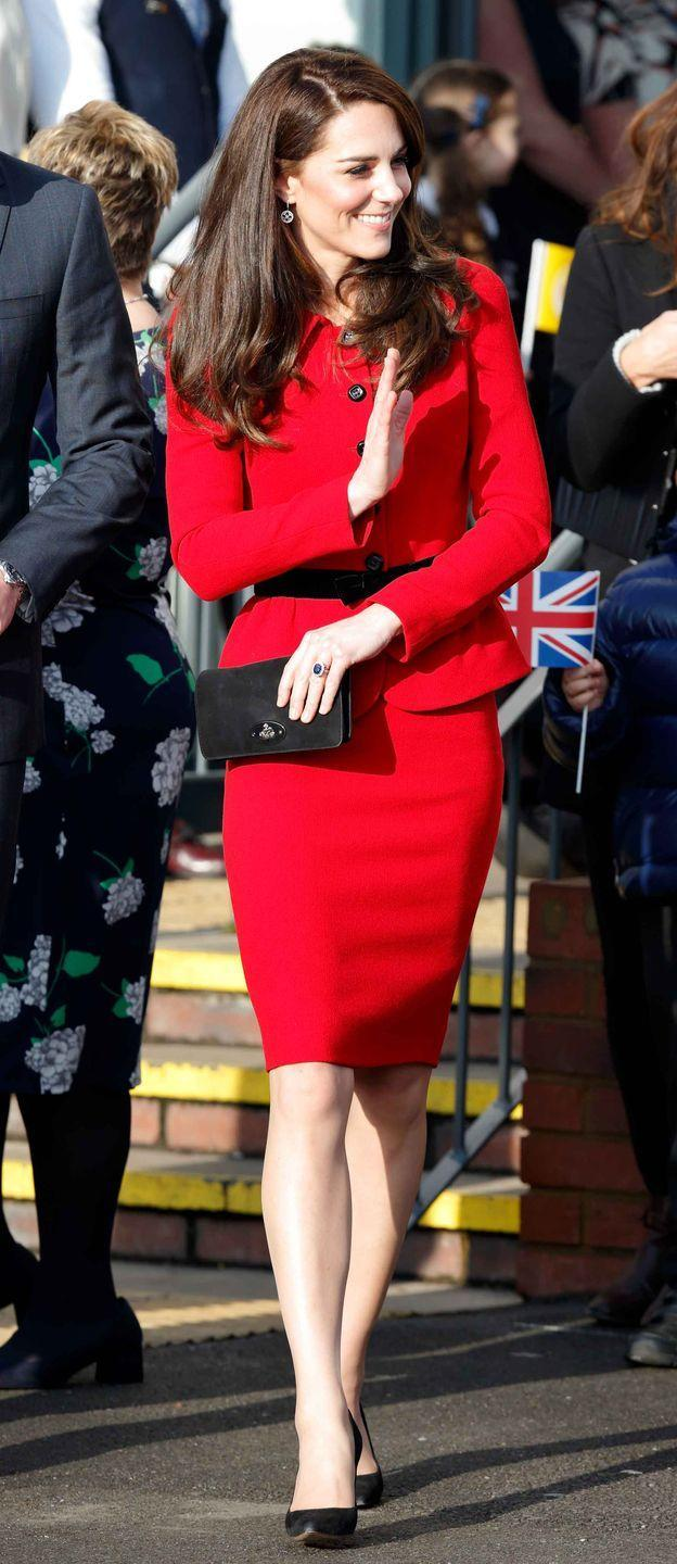 <p>During a Place2Be event, Kate wears a red peplum Luisa Spagnoli suit accented with a black velvet bow and black buttons.</p>
