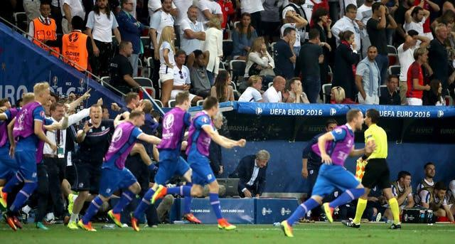 Roy Hodgson watches on as Iceland players and staff celebrate a 2-1 win over England at Euro 2016
