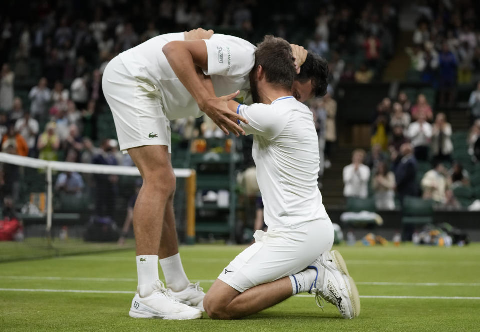Croatia's Mate Pavic, left, celebrates with playing partner Croatia's Nikola Mektic as they defeat Spain's Marcel Granollers and Argentina's Horacio Zeballos in the men's doubles final on day twelve of the Wimbledon Tennis Championships in London, Saturday, July 10, 2021. (AP Photo/Kirsty Wigglesworth)