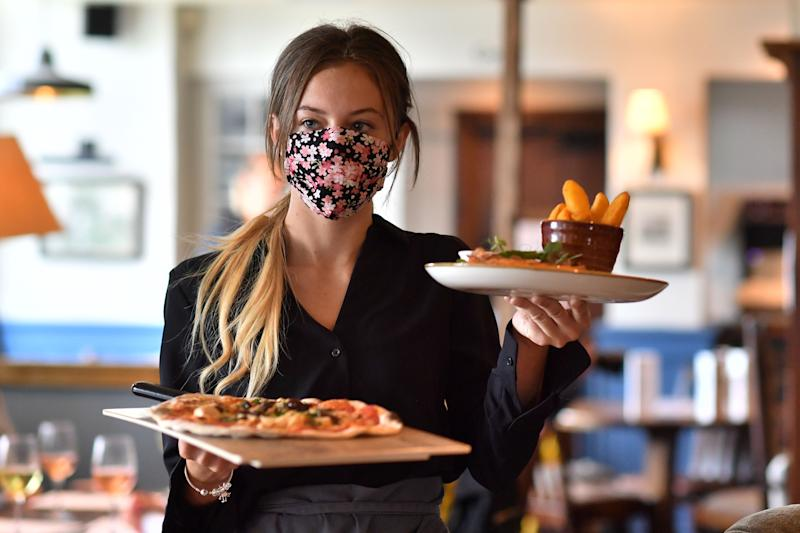 A staff member wears a face mask as she serves customers at the The Shy Horse pub and restaurant in Chessington, Greater London on July 4, 2020, on the first day of a major relaxation of lockdown restrictions during the novel coronavirus COVID-19 pandemic. Credit: Getty.
