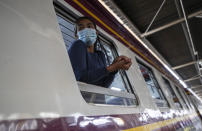 A passenger looks out from window on train bound for northeastern province of Ubon Ratchathani, at Hua Lamphong Railway Station in Bangkok, Thailand, Friday, April 9, 2021. Thai authorities were struggling Friday to contain a growing coronavirus outbreak just days before the country's traditional Songkran New Year's holiday, when millions of people travel around the country. (AP Photo/Sakchai Lalit)