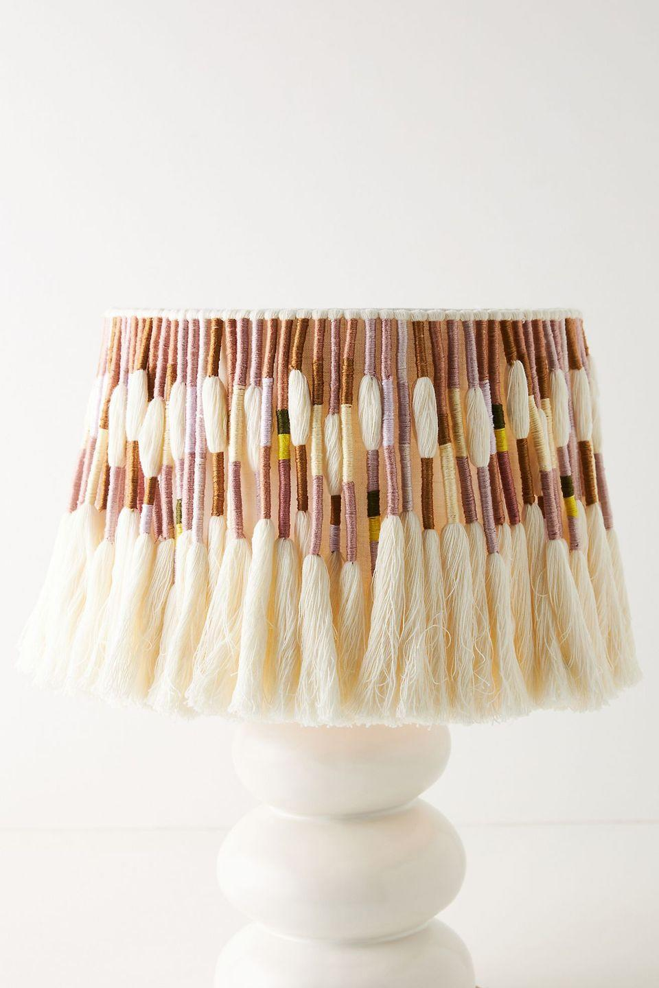 """<p>Here's another lampshade that celebrates the unique inconsistencies of handcrafted objects. This tasselled shade has an irresistible texture, mixing creamy and coloured cotton threads. A piece for both modern and vintage design schemes, it's an eye-catching accent wherever you put it.<br></p><p><strong>Shop now: <a href=""""https://www.anthropologie.com/en-gb/shop/corrine-tasseled-lamp-shade?category=home-lighting&color=066&type=REGULAR&quantity=1"""" rel=""""nofollow noopener"""" target=""""_blank"""" data-ylk=""""slk:Corrine Tasseled Lamp Shade ay Anthropologie"""" class=""""link rapid-noclick-resp"""">Corrine Tasseled Lamp Shade ay Anthropologie</a></strong></p>"""