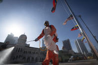 A city hall worker sprays a disinfectant at Merdeka Square, or independence square, situated in front of the Sultan Abdul Samad Building, background, in Kuala Lumpur, Malaysia, Saturday, Oct. 17, 2020. Malaysia will restrict movements in its biggest city Kuala Lumpur, neighboring Selangor state and the administrative capital of Putrajaya from Wednesday in an attempt to curb a sharp rise in coronavirus cases. (AP Photo/Vincent Thian)
