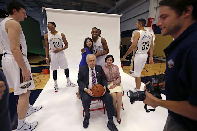 New Orleans Pelicans Eric Gordon (10) hugs team co-owner Rita Benson LeBlanc as they set up for a group photo with owner Tom Benson, seated, and his wife Gayle Benson, at the Pelicans NBA basketball media day in Metairie, La., Monday, Sept. 29, 2014. At left are Pelicans Omer Aski, Anthony Davis (23) and at right are Ryan Anderson (33) and NBA photographer Layne Murdoch, Jr. (AP Photo/Gerald Herbert)