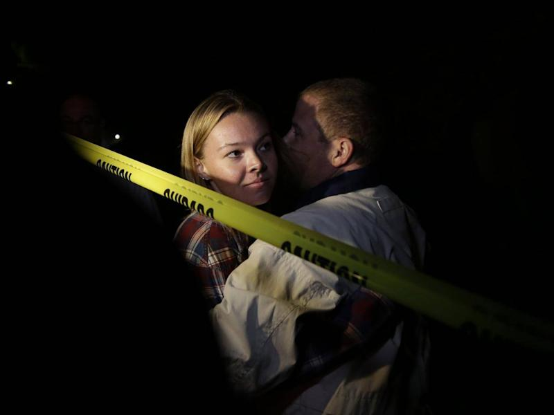 Teylor Whittler is hugged by her father after she fled the Borderline Bar (EPA)
