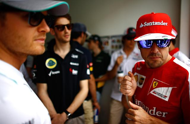 SAKHIR, BAHRAIN - APRIL 21: L-R) Nico Rosberg of Germany and Mercedes GP, Romain Grosjean of France and Lotus and Fernando Alonso of Spain and Ferrari look on prior to the Bahrain Formula One Grand Prix at the Bahrain International Circuit on April 21, 2013 in Sakhir, Bahrain. (Photo by Vladimir Rys/Getty Images)