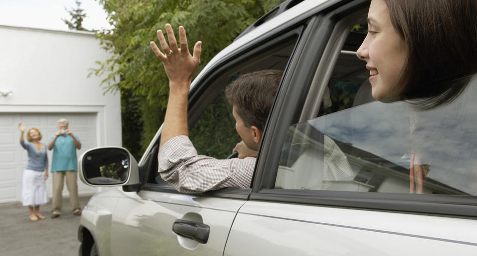 A man waves to a couple from a car. Source: Getty Images