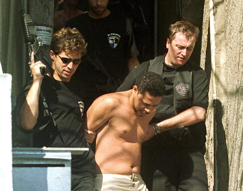 Ending a massive manhunt, drug trafficker Elias Pereira da Silva, aka Elias Maluco, is taken into custody after being arrested in the Complexo do Alemao slum in Rio de Janeiro, Brazil on Thursday Sept. 19, 2002. Elias Maluco is accused of killing journalist Tim Lopes.(AP Photo/Wilton Junior-AE)