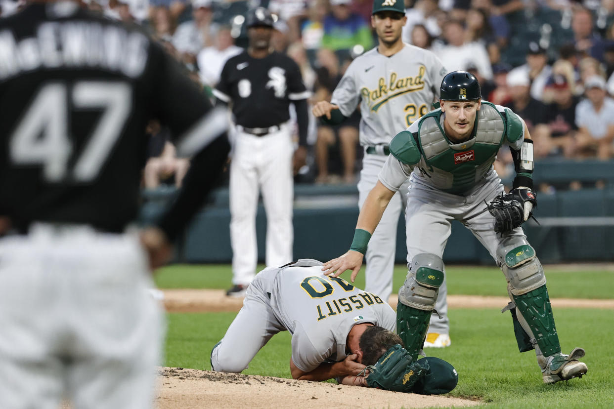 Aug 17, 2021; Chicago, Illinois, USA; Oakland Athletics catcher Sean Murphy (12) checks on starting pitcher Chris Bassitt (40) who covers his face after being hit by a ball hit by Chicago White Sox left fielder Brian Goodwin during the second inning at Guaranteed Rate Field. Mandatory Credit: Kamil Krzaczynski-USA TODAY Sports