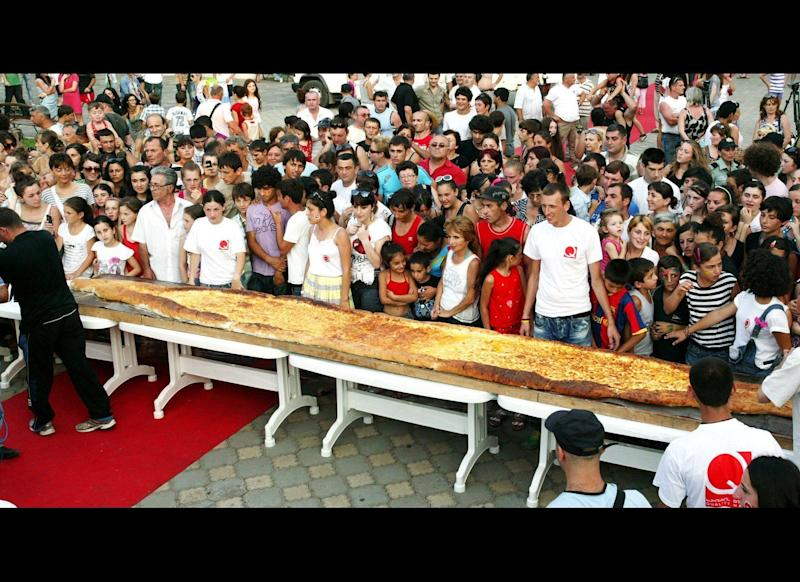 People look at a huge khachapuri (Georgian cheese pastry) in central Batumi on July 28, 2011. The cake was baked using 100 eggs, 90 kilograms of cheese, 150 kilograms of flour, has 8 meters length and was eaten within 1minute 32 seconds by people at a street.