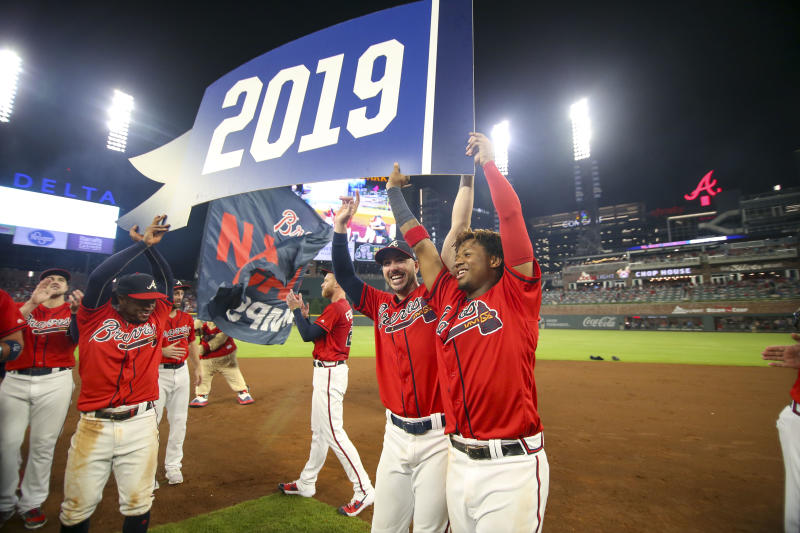 Atlanta Braves second baseman Ozzie Albies (1) and right fielder Matt Joyce (14) and center fielder Ronald Acuna Jr. (13) hold up the pennant after clinching the NL East division title on Sep 20, 2019 in Atlanta, Georiga. (Brett Davis-USA TODAY Sports)